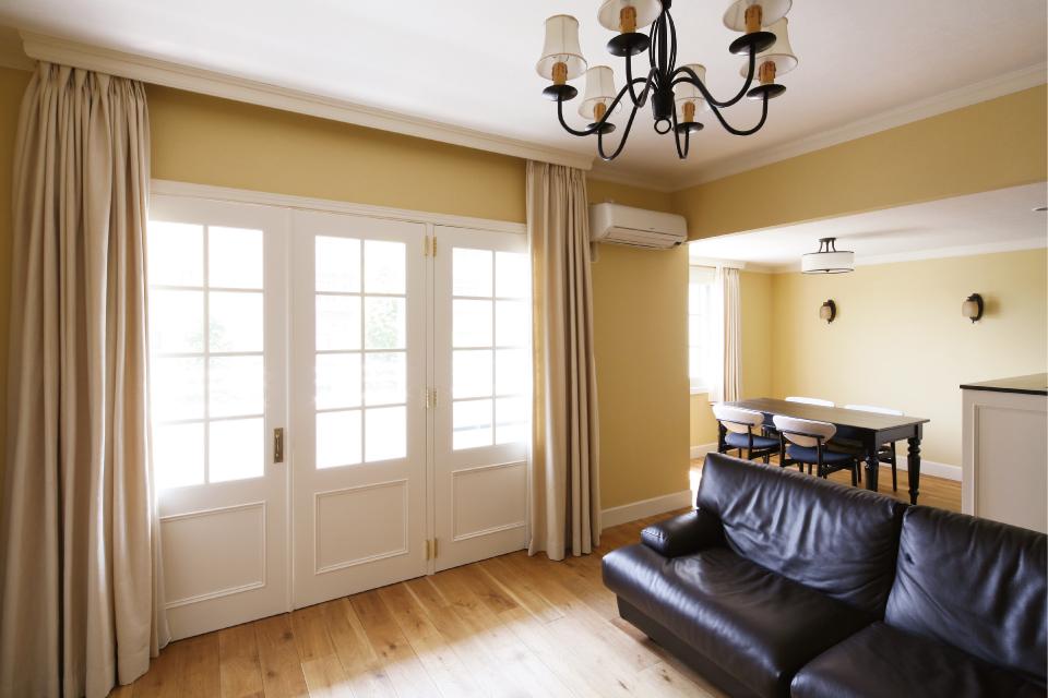 淡いレモンイエローが印象的なLDK。映画『最後の恋のはじめ方』に登場するN.Y.のアパートの世界観を再現。床はオーク無垢材フローリングに、天井にはモールディングを取付け、窓はすべてインナーサッシで仕上げた