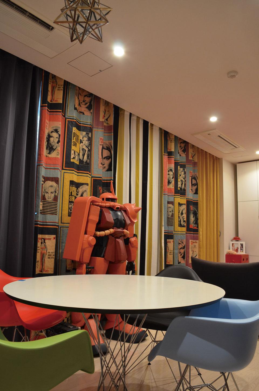 ガンダム好きのオーナーの趣味を反映したリビング。「ザク」のプラモデルを中心に、オレンジをアクセントカラーとし、プリント柄やストライプ、無地を組み合わせ、幅570cmの窓を6枚のカーテンで構成している。1枚1枚取り外せるので、気分によってカーテンの配置の並びを変えることも可能。ユニークな発想が空間に洗練された遊びを演出している。