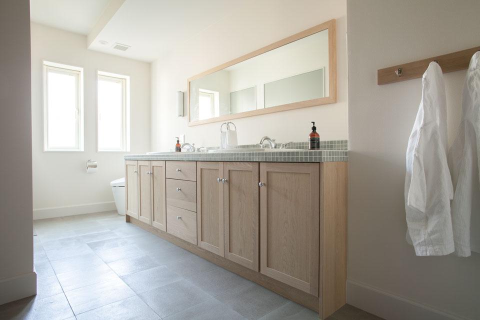 グレーを基調に広々とした洗面室には、「FILE」オリジナルのタイルを使用。リラックスした空気感を大切にデザインし、充実した収納家具の設置により、自然と片づけられる環境を生み出した。
