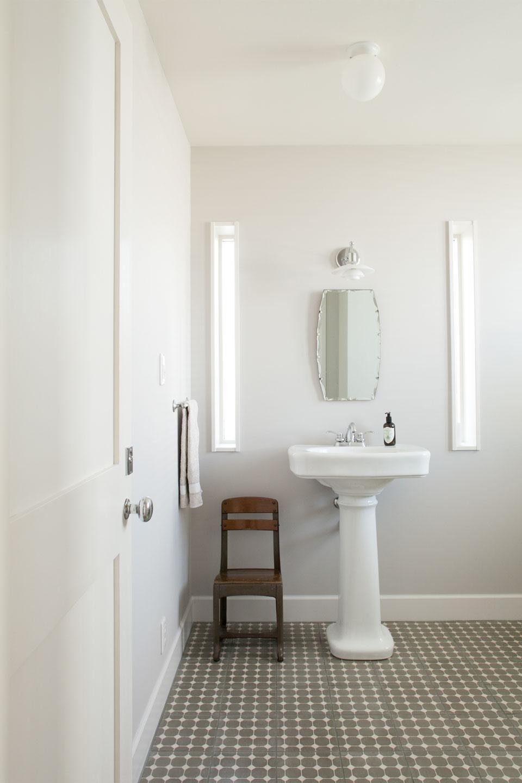 ポルトガルから輸入したタイルを敷いたトイレ。ホワイトペイントとの調和で柔らかい雰囲気に包まれている。
