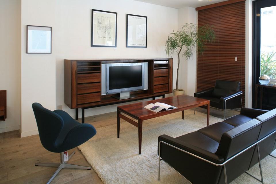 希少価値の高いローズウッドを使用したテレビボード。扉はじゃばらのデザインで、閉じてテレビを隠すことができる。細い脚が空間に軽やかさと洗練さを与える。