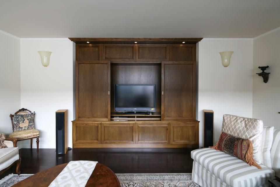 壁に埋め込んだ形にしたいという要望を受け、制作したオーク材を使ったテレビボード。上部に取り付けたさりげない3つのダウンライトがポイント。