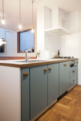 パリのアパートメントにありそうな雰囲気のあるキッチン。収納扉の取っ手には、デッドストックの北欧のパーツを使用。グリーンとブルーの中間色の扉の色合いが愛らしい。
