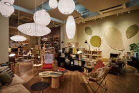 大小さまざまなバブルランプと、壁を彩るnanimarquinaのラグ「Quill」が印象的なリビングシーン。その奥には書斎をイメージさせる落ち着いた空間が広がっている。