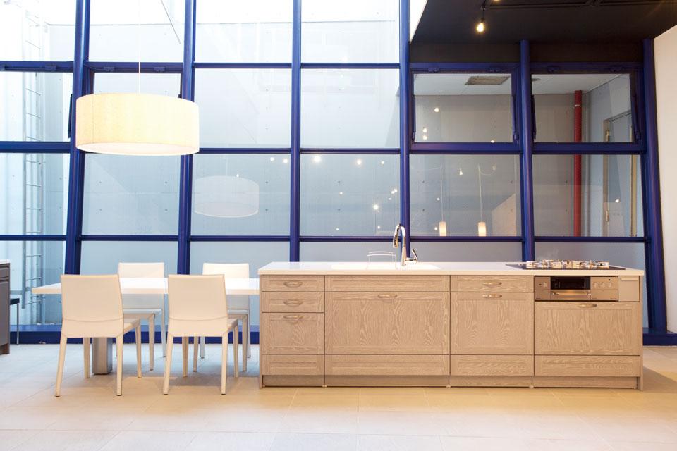 アイランド型のシステムキッチンは、ダイニングテープルを一直線に並べて美しく。キッチンもインテリアなのだということがよく分かる一例だ。キッチンの扉に施された意匠は「框細工」。